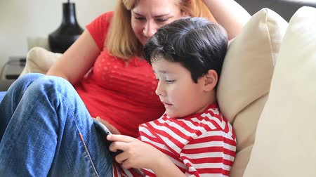 nanny holding : Mother And Son Using Digital tablet In The Living Room Stock Footage