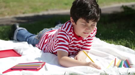 stáří : Child drawing on the grass
