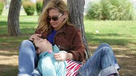 sorumluluk : Mother with son resting in the park Stok Video
