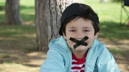 çabaları : chatty child covers his mouth with sellotape Stok Video