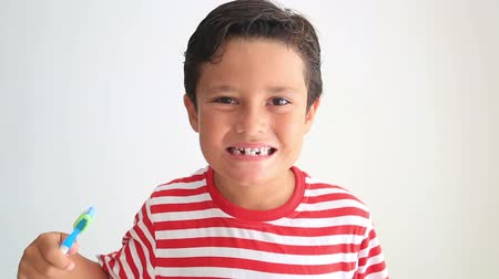 escovação : Child brushing and showing his missing tooth Vídeos