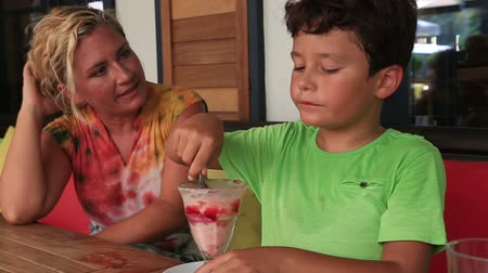 сладости : Child eating ice cream at the restaurant with his mother