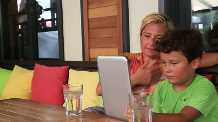 домашнее задание : Mother and son with digital tablet at cafe Стоковые видеозаписи