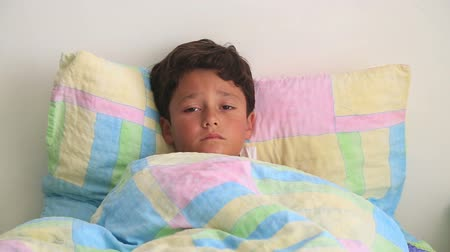doente : Sick child lying in bed and coughing