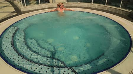 джакузи : woman relaxing in an outdoor jacuzzi
