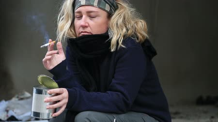 pleading : Homeless woman begging and smoking cigarette