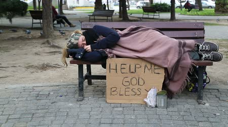 pleading : Homeless woman resting on a park bench Stock Footage
