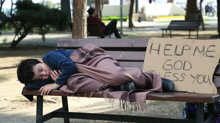 pleading : Homeless, sick child lying on bench Stock Footage