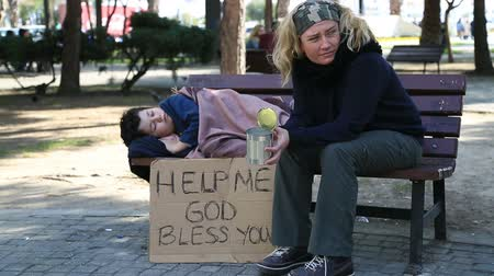 fome : Homeless, sick family begging on a park bench