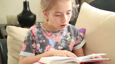 olvasás : Beautiful little girl sitting on sofa reading book