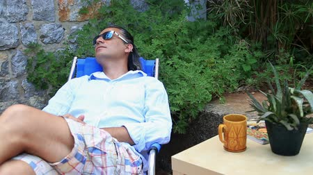 devanear : Sleepy man relaxing in the garden Stock Footage