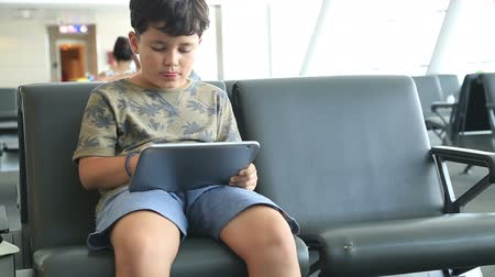 cena não urbana : Young boy gaming on tablet computer while waiting at the airport. Vídeos
