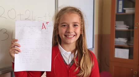 сообщить : Happy cute little girl showing exam paper with a plus in the classroom
