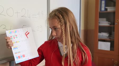 сообщить : Unhappy little student  holding school paper with F grade Стоковые видеозаписи