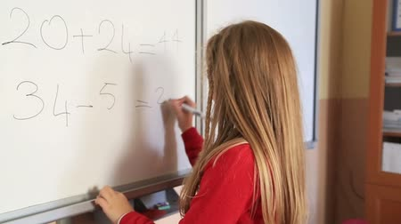 deha : Little schoolgirl solving mathematic problem on the blackboard