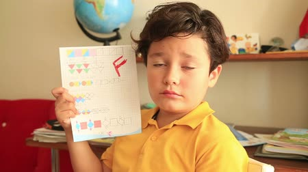 shameful : Unhappy little student  holding school paper with F grade Stock Footage