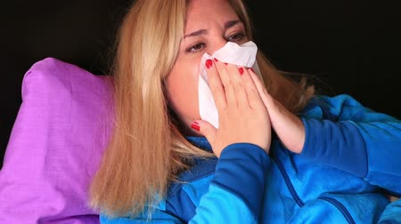 üfleme : Frustrated sick woman lying on a bed and sneezing Stok Video