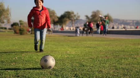 sport dzieci : Young boy kicking ball in the grass outdoors