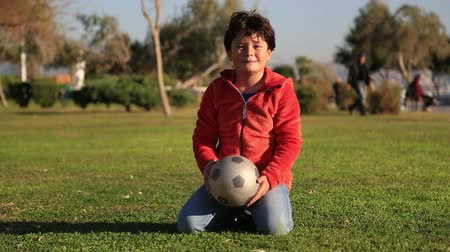 futbol topu : Portrait of a  happy clumsy  child with a ball smiling to a camera Stok Video