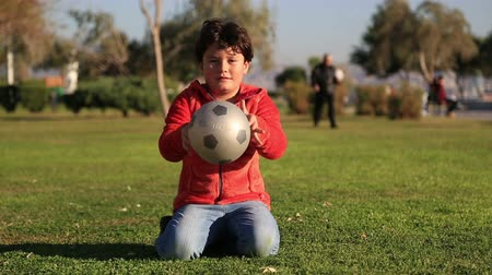 sport dzieci : Portrait of a  happy clumsy  child with a ball smiling to a camera Wideo