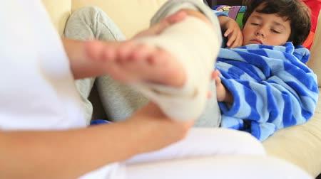 капелька : Nurse bandaging little boy ankle