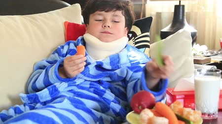 pihenő : Portrait of a little boy  with a neck brace sitting on a couch, eating  cucumber and carrot