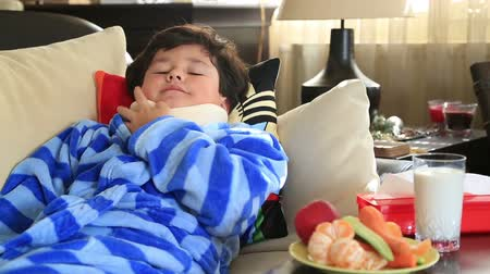 страдать : Sleepiness,painful little boy with a neck brace lying on a sofa and resting