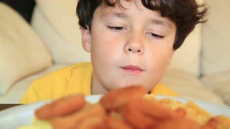 sağlıksız : Young boy eating fried potatoes and crispy onion rings