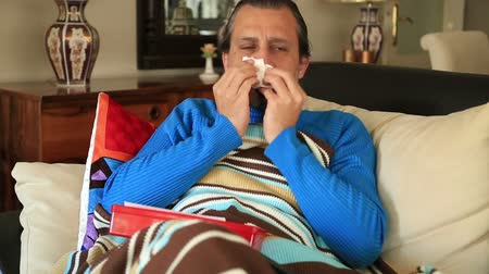 cold : Sick man caught a cold, lying on a couch with blanket and  sneezing Stock Footage