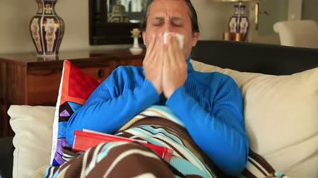 doente : Sick man caught a cold, lying on a couch with blanket and watching tv