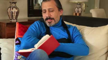 bandaj : Painful man with injured arm and bandage sitting on sofa and reading a book Stok Video