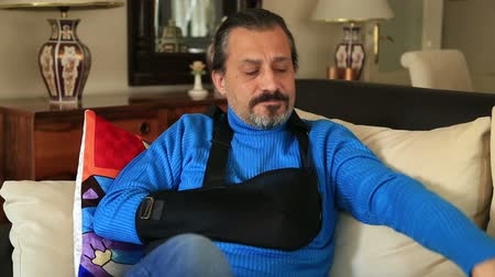 bandagem : Painful, bored man with a broken arm wearing arm brace sitting on a sofa