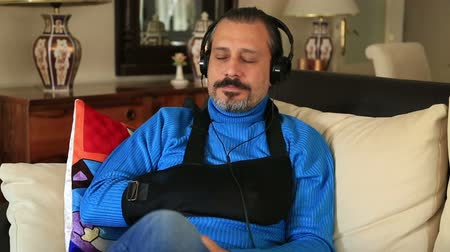 painéis : Painful man with a broken arm wearing arm brace sitting on a sofa and listening to music Stock Footage