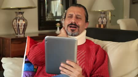krk : Painful man with neck brace sitting on  sofa and watching movie on digital tablet computer