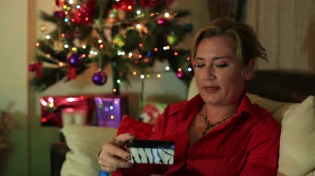 exiting : Portrait of surprised woman with gift box, sitting on the sofa near the christmas tree