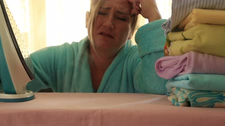 ütüleme : Depressed, tired housewife ironing clothes Stok Video