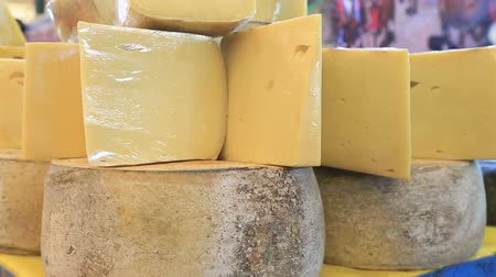 pieces of cheese : Cheese wheels stacked on the marketplace Stock Footage