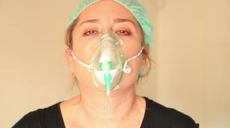 oksijen : Portrait of a sick, sad  woman wearing a oxygen mask and looking at the camera