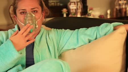 oksijen : Portrait of a diseased  woman wearing a oxygen mask sitting at the sofa at home Stok Video