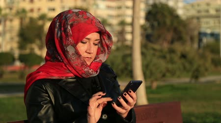 başörtüsü : Arabic muslim woman wearing red scarf, sitting on a park bench and using mobile smart phone Stok Video