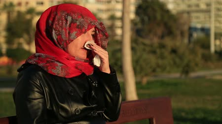 cover : Arabic muslim woman wearing red scarf, sitting on a park bench and sneezing