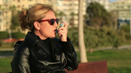 asthma : Woman seated on a park bench taking asthma treatment with inhaler
