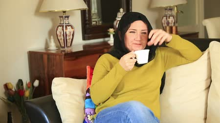 feliz : Muslim woman sitting on a sofa and smiling at the camera