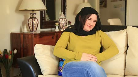 żołądek : Sick muslim woman sitting on a sofa and having abdominal pain