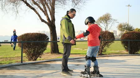 öğretim : Father teaching his little son roller skating and having fun time