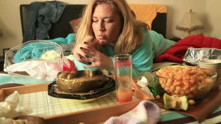 жадный : Portrait of a woman in depression lying on a bed and eating junk food