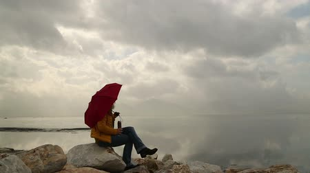 be sad : Woman with umbrella sitting alone in rocks on the seaside bank and be lonely Stock Footage