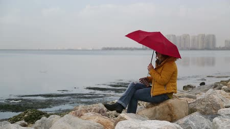 одиноко : Woman with umbrella sitting alone in rocks on the seaside bank and be lonely, rainly day