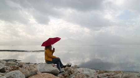 lonely : Woman with umbrella sitting alone in rocks on the seaside bank and be lonely Stock Footage