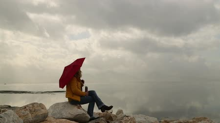 to be alone : Woman with umbrella sitting alone in rocks on the seaside bank and be lonely, rainly day time